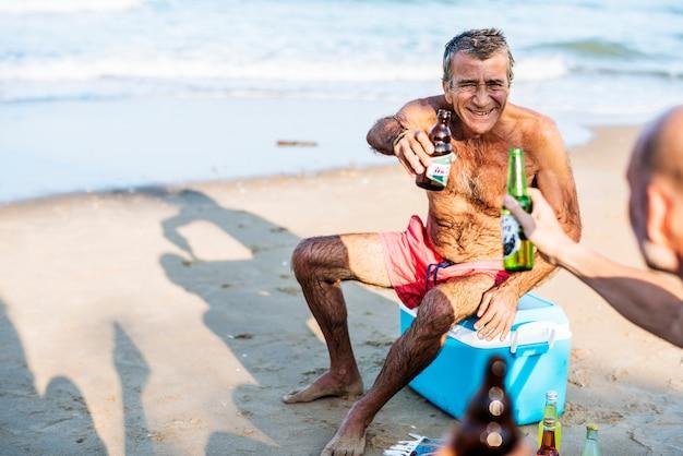 Amigos mayores colgando en la playa