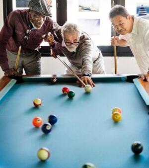 Amigos mayores jugando al billar