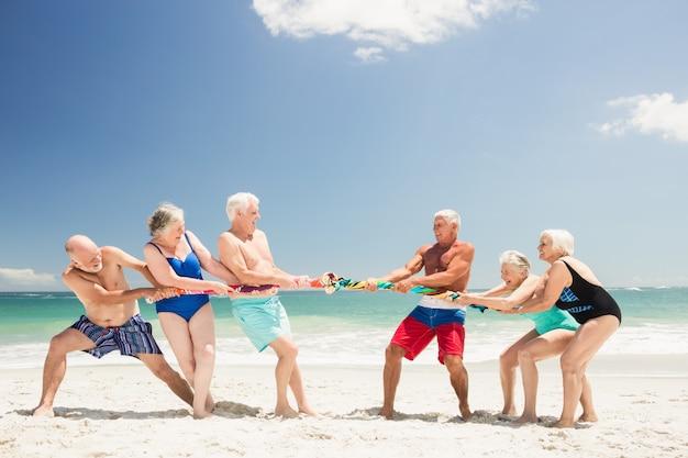 Amigos mayores jugando tira y afloja