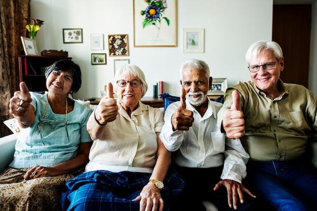 Amigos mayores que gesticulan los pulgares para arriba