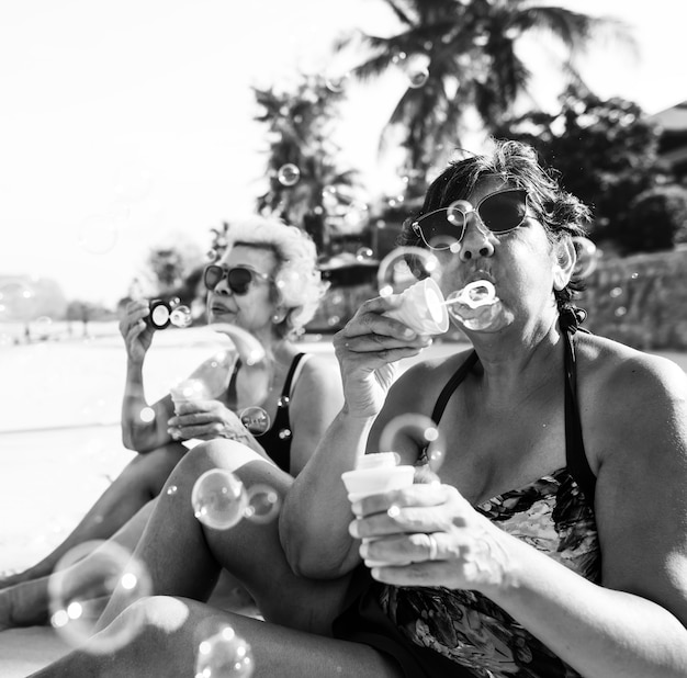 Amigos mayores que soplan burbujas y refrigeración en la playa