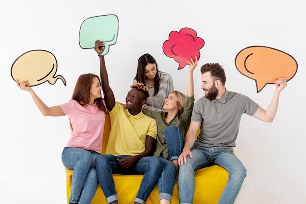 Amigos mirándose y sosteniendo una burbuja de chat