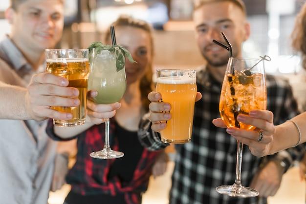 Amigos mostrando vasos de bebidas cócteles