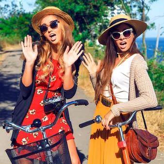 Amigos de mujer hipster juntos caminando con bicicletas en el parque junto al mar.