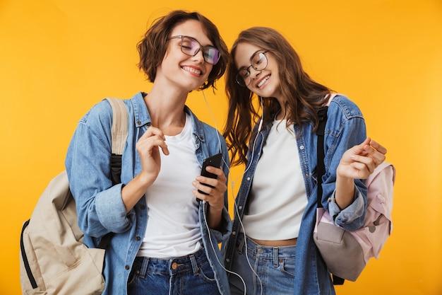 Amigos de las mujeres aisladas sobre la pared amarilla mediante teléfono móvil escuchando música con auriculares.