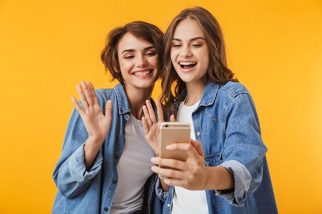 Amigos de las mujeres jóvenes aislados sobre la pared amarilla hablando por teléfono móvil agitando.