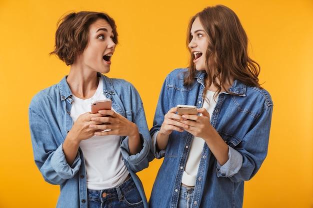 Amigos de las mujeres jóvenes aislados sobre la pared amarilla mediante teléfonos móviles.