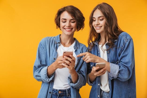 Amigos de las mujeres jóvenes emocionales felices posando aislado sobre pared amarilla usando teléfonos móviles.