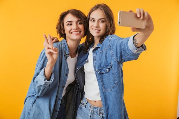 Amigos de las mujeres jóvenes emocionales posando aislado sobre pared amarilla toman un selfie por teléfonos móviles.