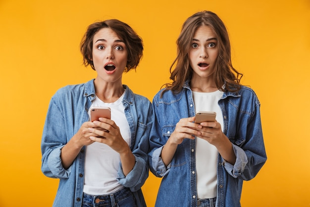 Amigos de mujeres jóvenes emocionales sorprendidos posando aislado sobre pared amarilla usando teléfonos móviles.