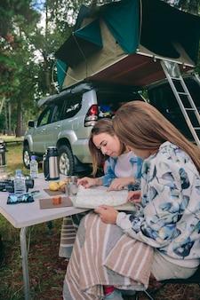 Amigos de las mujeres jóvenes que buscan hoja de ruta en un camping con su vehículo en el fondo