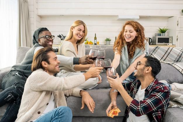 Amigos multiculturales jovenes alegres que tintinean con copas de vino tinto mientras hacen tostadas en el sofá en la fiesta de casa
