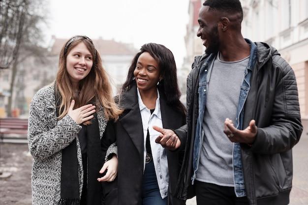 Amigos multiculturales riendo juntos tiro medio