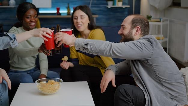Amigos multiculturales socializando mientras están sentados en el sofá en la sala de estar a altas horas de la noche bebiendo cerveza e ...