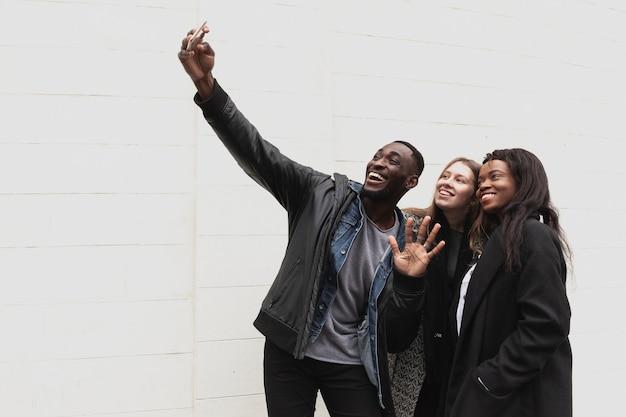 Amigos multiculturales tomando espacio de copia selfie