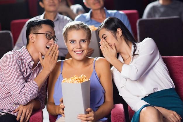 Amigos multiétnicas alegre que se sienta en el cine