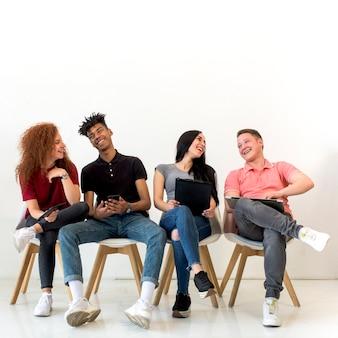 Amigos multiétnicos alegres que sostienen el artilugio electrónico que se sienta en sala de clase