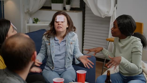 Amigos multiétnicos bebiendo cerveza mientras juegan adivina quién usando notas adhesivas grupo de multirac ...
