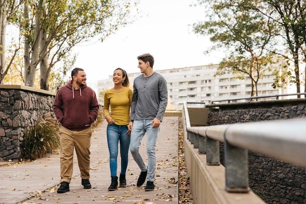 Amigos multiétnicos caminando en otoño