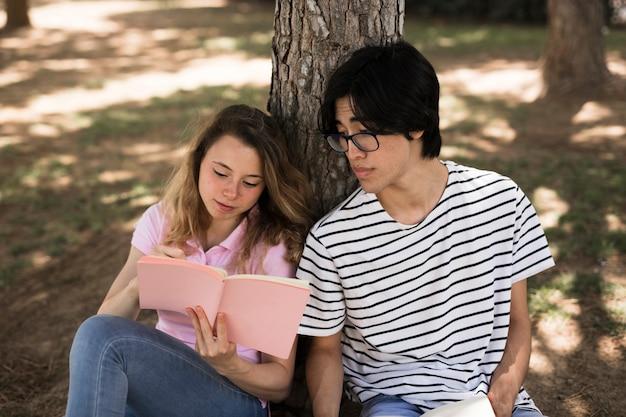 Amigos multiétnicos leyendo un cuaderno y apoyándose en un árbol