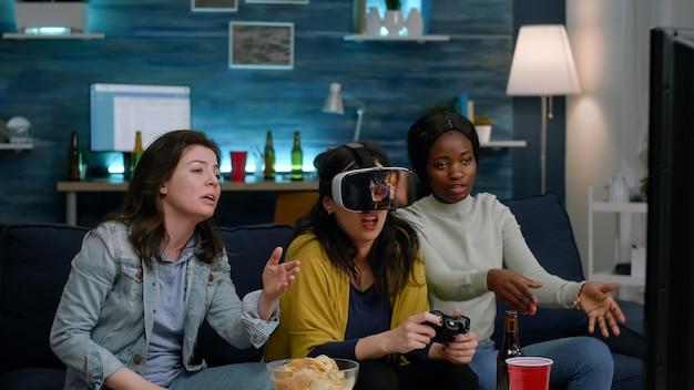 Amigos multiétnicos que pierden videojuegos usando auriculares de realidad virtual y un grupo de joystick de personas g ...