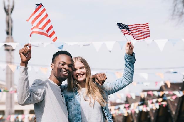 Amigos multiétnicos que sostienen banderas americanas en manos extendidas