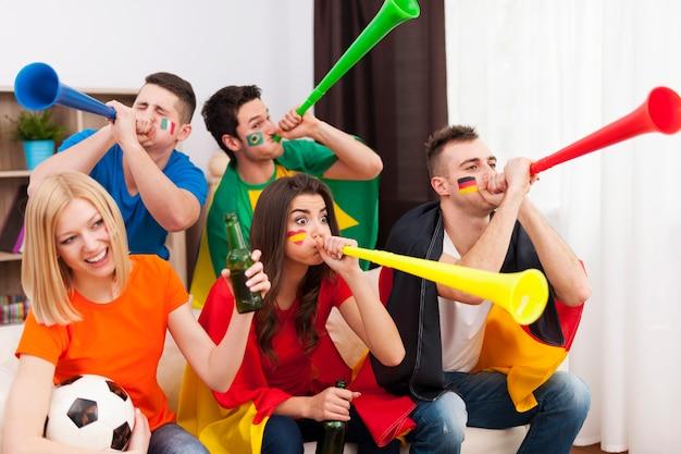Amigos multinacionales soplando por vuvuzela durante el partido de fútbol