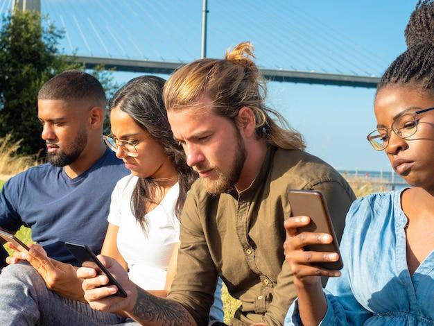 Amigos multirraciales enfocados que usan teléfonos inteligentes
