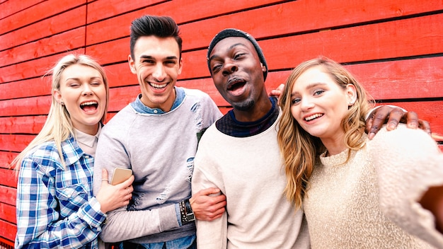 Amigos multirraciales felices tomando selfie de grupo en el fondo de madera roja