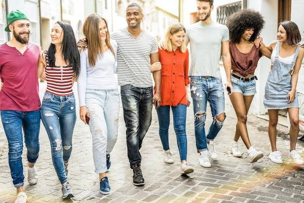 Amigos multirraciales milenarios caminando y hablando en el centro de la ciudad
