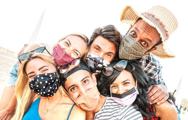 Amigos multirraciales milenarios que toman selfie sonriendo detrás de las mascarillas