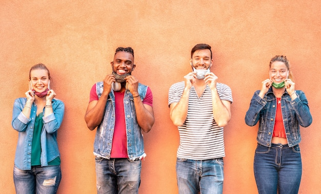 Amigos multirraciales milenarios sonriendo con máscara facial después de reabrir el cierre