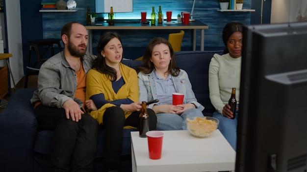 Amigos multirraciales que cambian de canal en la televisión hasta que encuentran una película divertida