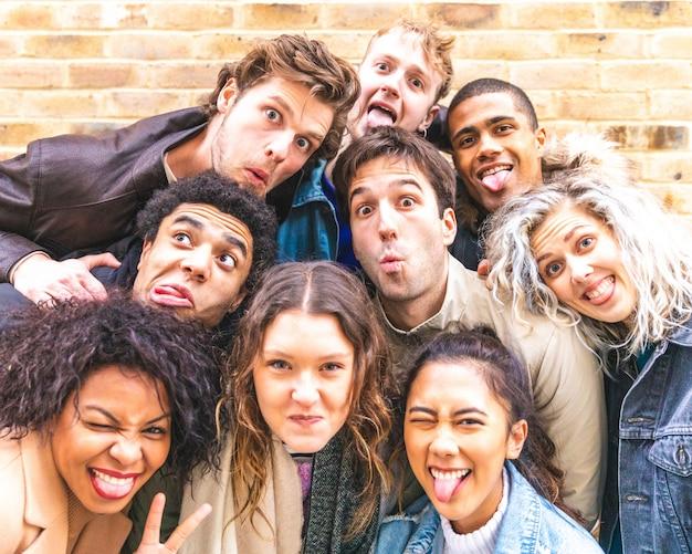 Amigos multirraciales que toman selfie y hacen caras graciosas.