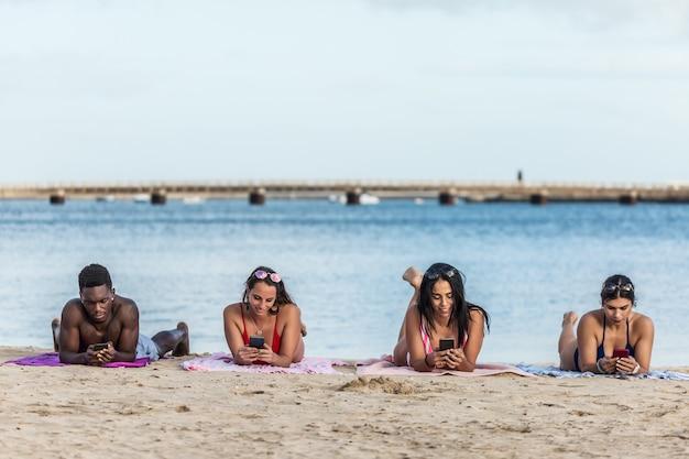 Amigos multirraciales con teléfonos inteligentes en la playa