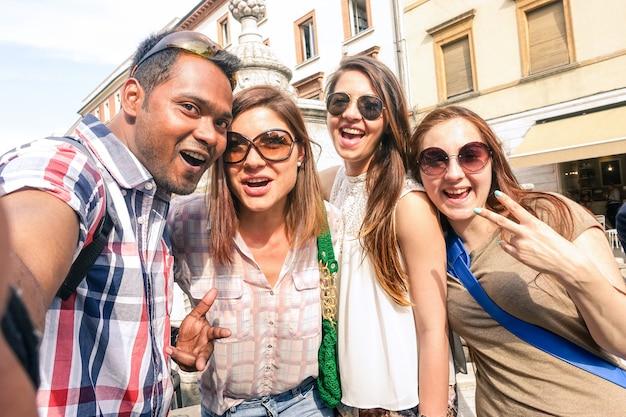 Amigos multirraciales tomando autofotos en el tour por la ciudad.