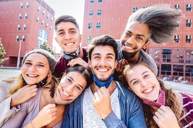 Amigos multirraciales tomando selfie con mascarilla abierta en el campus universitario