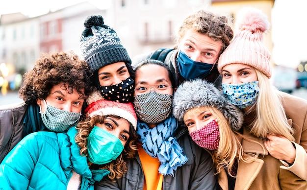 Amigos multirraciales tomando selfie con mascarilla y ropa de invierno