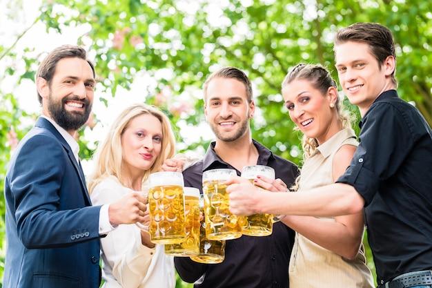 Amigos o colegas en el jardín de la cerveza después del trabajo brindando con bebidas