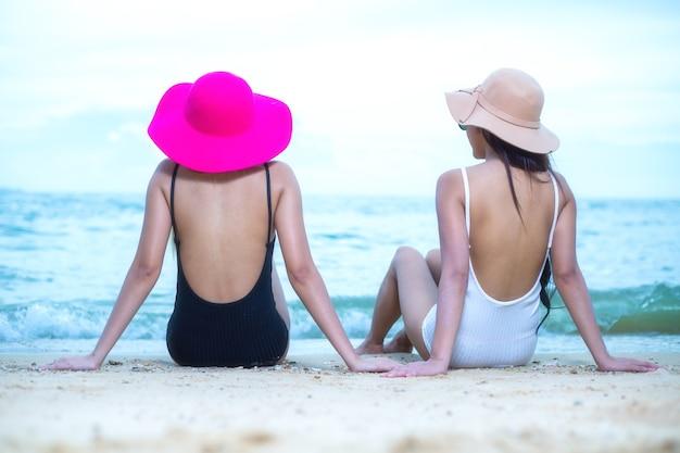 Amigos de pareja, mujeres asiáticas felices en la playa durante las vacaciones de verano
