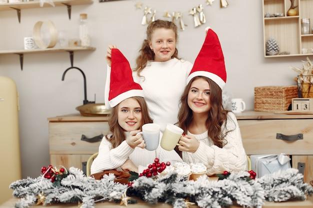 Los amigos pasaban tiempo en casa. dos chicas beben té. mujer con sombrero de santa.