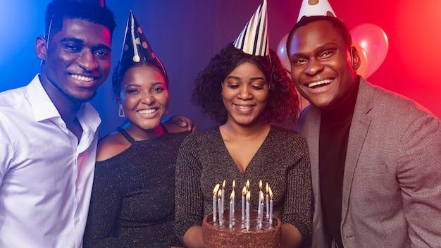 Amigos y pastel de feliz cumpleaños