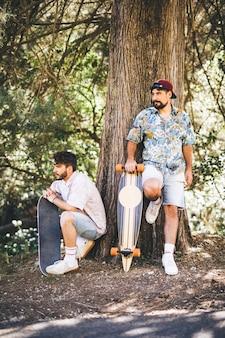 Amigos con patinetas en bosque