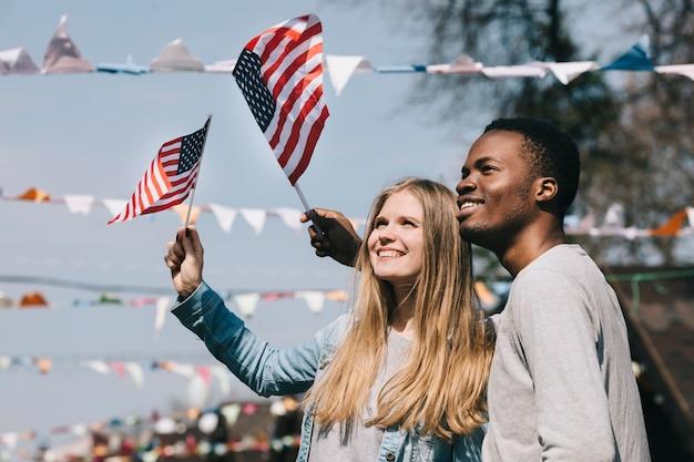 Amigos patrióticos multiétnicos ondeando banderas de estados unidos