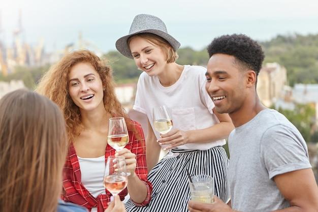 Amigos de pie en el balcón admirando los paisajes de la ciudad mientras beben cócteles