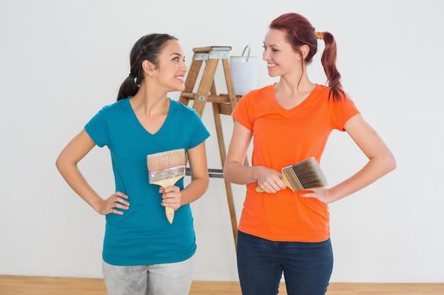 Amigos con pinceles y escalera en una casa nueva