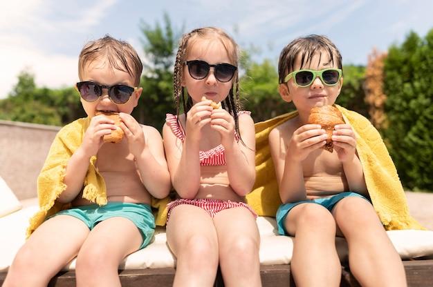 Amigos en la piscina comiendo
