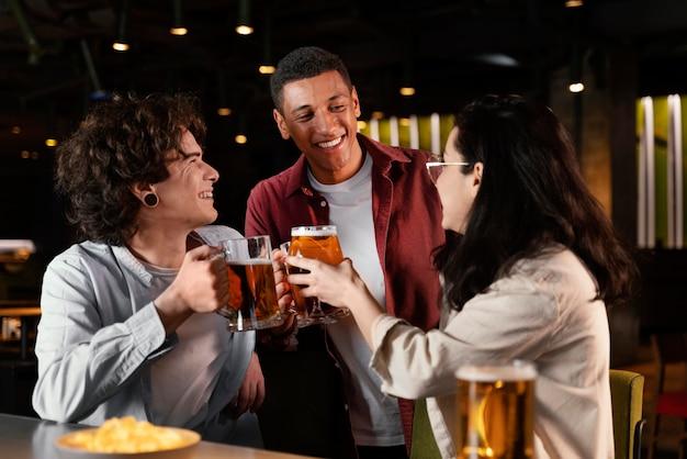 Amigos de plano medio charlando en el pub