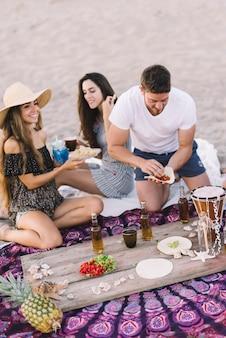 Amigos en la playa con bebida en una tabla