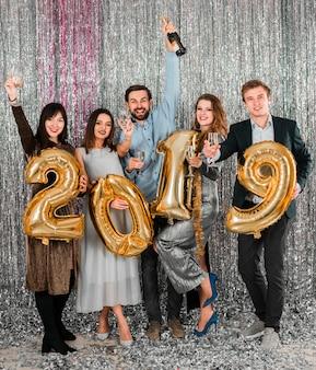 Amigos posando con globos dorados fiesta año nuevo
